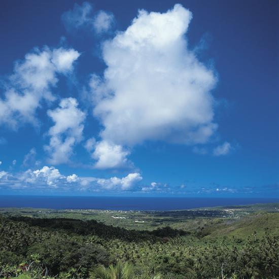 Fluffy White Clouds Over a Blue Ocean and Beach--Photographic Print