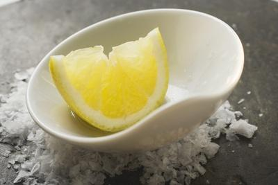 Lemon Wedge with Olive Oil in a Small Bowl on Salt