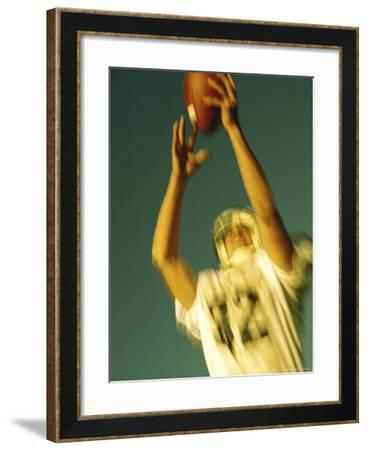 Football Player Reaching Up To Catch a Ball--Framed Photographic Print