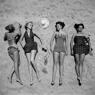 Four Models Showing Off the Latest Bathing Suit Fashions While Lying on a Sandy Florida Beach-Nina Leen-Photographic Print