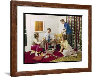 Four Smartly-Dressed Teenagers Having Cocktails around a Record Player--Framed Photographic Print