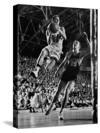 Burke Scott of Hoosiers Basketball Team Leaping Through Air Towards Lay Up Shot at Basketball Hoop