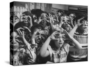Classroom Full of Students Circling Fingers Around Eyes in Form of Glasses During Music Class by Francis Miller