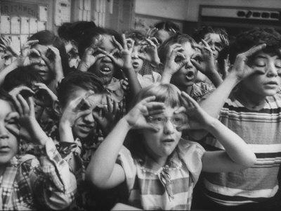 Classroom Full of Students Circling Fingers Around Eyes in Form of Glasses During Music Class