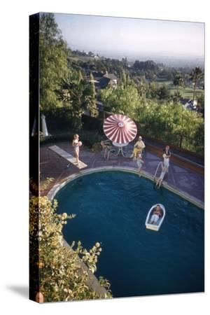 A Family at their Backyard Swimming Pool, in Foreground a Floating Rowboat with Boy Aboard