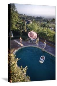 A Family at their Backyard Swimming Pool, in Foreground a Floating Rowboat with Boy Aboard by Frank Scherschel