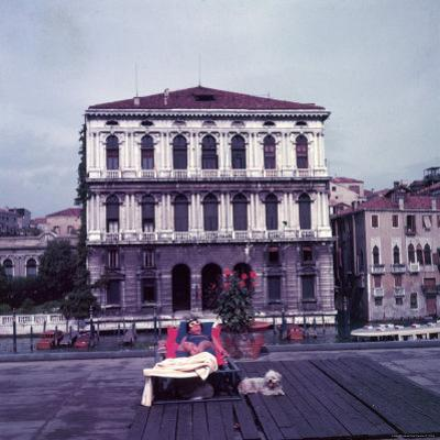 Heiress Peggy Guggenheim Sunbathing on Terrace of Venier Dei Leoni Palace on Grand Canal in Venice