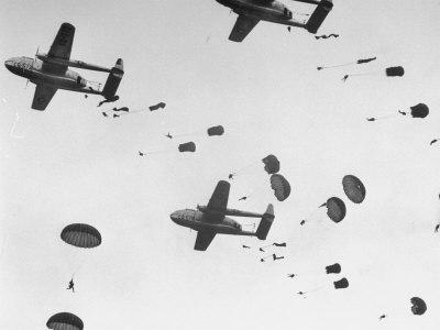 """Scores of Paratroopers Dropping from C-82 """"Flying Boxcar"""" and Landing on Level Ground"""