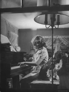 """Suzy Creech, Typical Girl Known as a """"Pigtailer"""" at Home Playing the Piano by Frank Scherschel"""