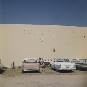 Tourists in Bathing Suits by Parked Cars and Climbing the Sleeping Bear Sand Dunes, Michigan, 1961 by Frank Scherschel