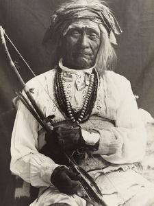 An Old War Chief, Seated On a Chair, Poses with a Bow and Arrows by Frederick I. Monsen