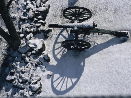 Fresh Snowfall Outlines a Cannon in This Winter View of Gettysburg-Stephen St^ John-Photographic Print
