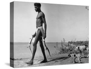 Australian Aborigine Man Bringing Back Two Monitor Lizards Known as Goannas to His Clan by Fritz Goro