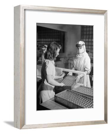 Sealed Vials of Penicillin Being Passed from the Sterile Production Room to Packaging Room