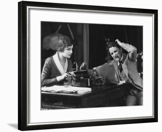 Frowning Manager Reviewing Secretary's Work--Framed Photo