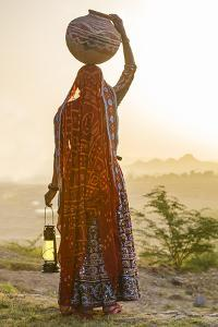 Ahir Woman in traditional colorful cloth carrying water, India by G&M Therin-Weise