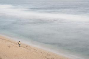 A Man Standing on a White Sand Beach by Gabby Salazar
