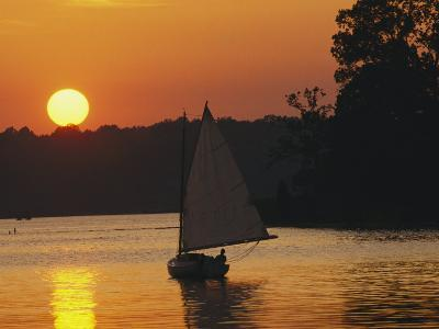 Gaff-Rigged Catboat Sails Along the Shoreline at Sunset-Skip Brown-Photographic Print