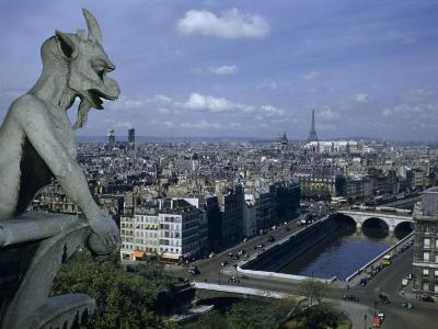 Gargoyle on Notre Dame Looks Down on a Densely Packed Cityscape-Justin Locke-Photographic Print