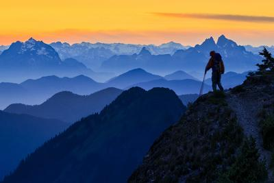 USA, Washington State. A backpacker descending from the Skyline Divide at sunset.