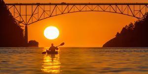 Washington, Woman Sea Kayaker Paddles before the Deception Pass Bridge at Sunset by Gary Luhm