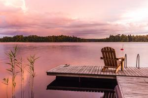 Wooden Lounge Chairs at Sunset on a Pier on the Shores of the Calm Saimaa Lake in Finland under a N by gdefilip