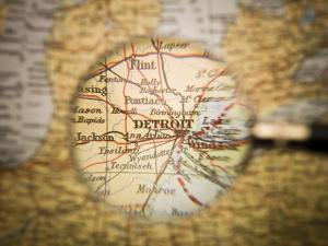 Magnifying Glass In Front Of A Detroit Map by gemenacom