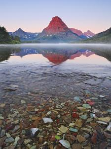 Dawn Light Sets the Peaks Aglow over Misty Two Medicine Lake, Glacier National Park, Montana, USA by Geoffrey Schmid