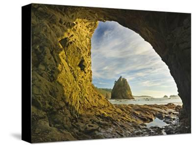 Wispy Cirrus Clouds and a Seastack Seen Through Hole in the Wall Accessible Only at Low Tide
