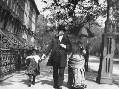 Incredibly Well Dressed Man, Woman and Child Walking by Perfect Brownstone Apartment Buildings
