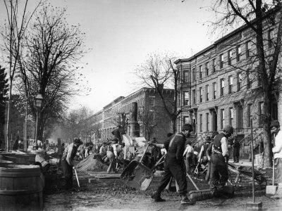 Many Men Hard at Work Paving a Street