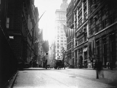 People and Horse Drawn Carts on Wall St, Where American Flags Fly from Buildings
