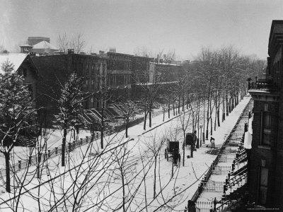 Woman sweeps snow off a snow-covered street lined with brownstones near two horse-drawn buggies.