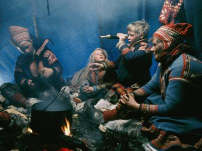 A Lapp Family Prepares a Meal in their Tent by George F^ Mobley