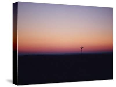 A Windmill Breaks the Flat Horizon of the Texas Panhandle at Dawn