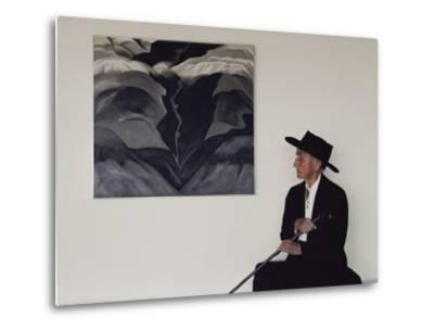 Painter Georgia O'Keeffe Sits before Her Vision of 'Black Place Iii'
