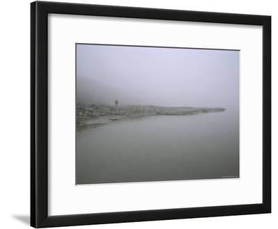 Solitary Figure on the Fog-Enshrouded Shore of the Okpilak River, Alaska