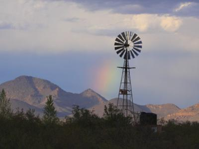 A Windmill on a Ranch with a Rainbow and Mountain Scenery by George Grall