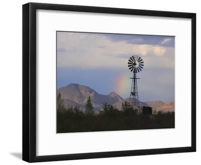 A Windmill on a Ranch with a Rainbow and Mountain Scenery