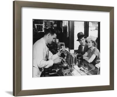 Bartender Pouring Beer For Young Couple in Bar