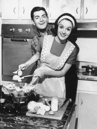Couple Standing in Kitchen, Smiling by George Marks
