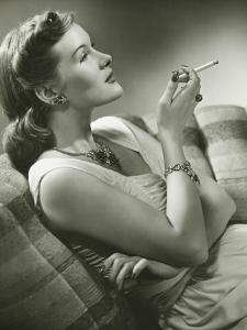 Elegant Woman Sitting on Couch, Smoking Cigarette by George Marks