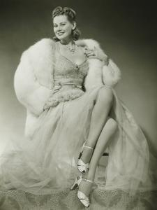 Glamorous Woman in Evening Dress Showing Legs, Posing in Studio by George Marks