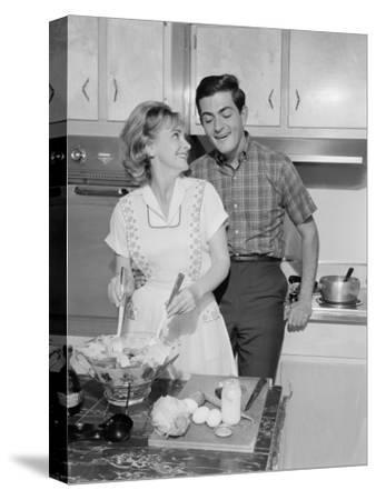 Mid Adult Couple in Kitchen, Woman Preparing Salad