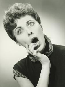 Shocked Woman With Fingers on Lips in Studio, Portrait by George Marks