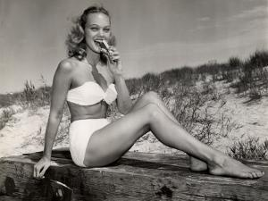Woman Eating a Hot-Dog at the Beach by George Marks