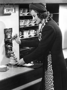 Woman Getting Coffee at Old Fashioned Machine by George Marks