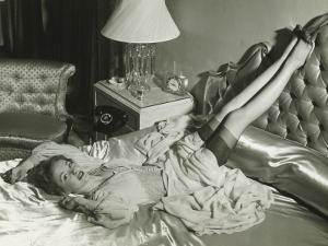 Woman Lying on Bed With Legs on Backrest, Elevated View by George Marks