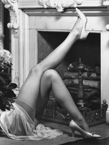 Woman Wearing Stockings Laying By Fireplace, Low Section by George Marks