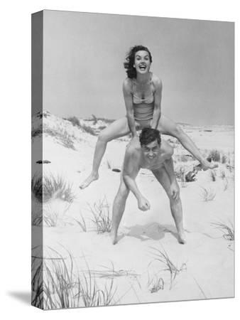 Young Couple on Beach, Woman Leap-Frogging Man, Portrait